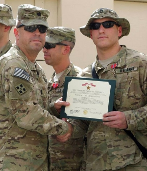 United States Army Staff Sergeant Kevin J. Buddy Edwards holds his Bronze Star Medal Certificate.
