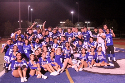 Football team and Cheer Leaders Pose with helmet after exciting win