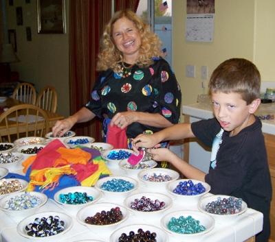 """The Marble Lady"" (Cathy Runyan) helps Luke Myers bag over 13,000 marbles for the fundraiser."