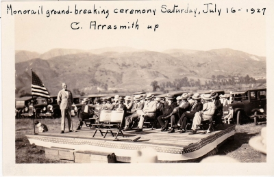 Groundbreaking ceremony for the Fillmore Mononrail which took place July 7th 1927. Pictured is Clarence Arrasmith, City Manager, standing. Seated L to R: Dock Wyatt (Santa Paula); Mayor W. H. Price; P. S. Coombs, VP Sespe Development Company; J. O. Groves, head engineer, Sespe Development Company; Joseph McNab, chairman of the ceremony; David J. Reese, Ed Goodenough; reporters.