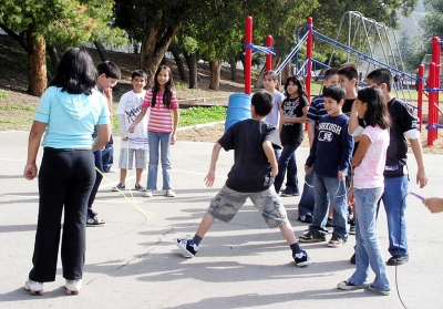 Fourth grade students take turns jumping rope.