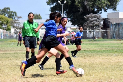 Forward Marlene Gonzales (front) races by the opposing player as Jadon Rodriguez (back) awaits a crossing pass to take a shot. Photo by Martin Hernandez.