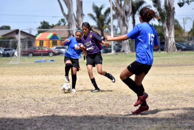 Two of our tireless mid-fielders, Fatima Alvarado (left) using some fancy footwork to get around the defender as Athena Sanchez (right) gets in position to receive the pass. Photo by Martin Hernandez.