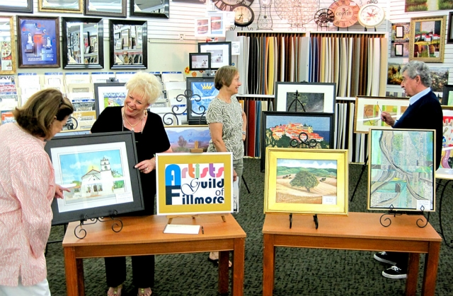 Luanne Perez and Jan Faulkner (both in center) are discussing the art works by the Artists Guild of Fillmore with interested Susan and Gil Rosas of Santa Barbara.