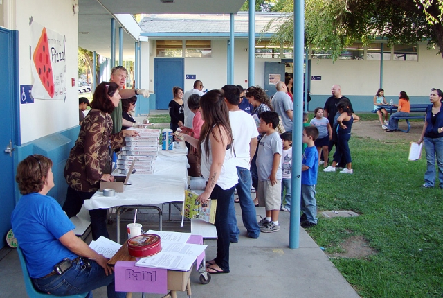 Back To School Night at San Cayetano was very busy in addition to classroom visits. Shown here are Mrs. Resor, the Elementary Band teacher looking for new recruits and Mrs. Overton and Mr. Meich are selling pizzas to raise money for additional classroom materials.