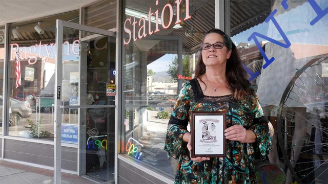 "Cindy Largey from Ragtyme Station with her 1st place award for ""Best Window Display Contest"" at this year's Dia De Los Muertos"" (Day of the Dead) event which was held downtown November 2nd. Photo courtesy Diego Rodrigues. Congratulations to Cindy Largey from Ragtyme Station who won First Place in the Fillmore downtown merchant ""Best Window Display"" contest for Dia De Los Muertos"" (Day of the Dead). The window display depicted a standing bride and a skeleton groom riding a vintage bicycle with their pet skeleton doggie holding a ""Just Married"" sign. The display filled the large window and the neon paint on the skeletons particularly stood out at night. On November 2, over 400 people attended the 4th Annual ""Dia De Los Muertos"" Day of the Dead celebrated, on Central Ave. in downtown Fillmore CA. Big Brothers & Big Sisters of Ventura County (BBBS) presented the event. BBBS would like to thank all the sponsors, volunteers, vendors and  other participants. A huge thank you to: Captain Dave Wareham, Pedro A. Chavez, Los Hermanos Herrera, Radio Lazer, DJ Limon, Ernie Villegas, Francisco's Fruits, La Fondita, E.J. Harrison & Sons, Inc., The Bumper Man. Inc., community members who created altar offerings, Jaime from The Fillmore Bicycle Hub, and to all of the Fillmore and Piru staff, elementary and high school students that participated. We would also like to thank the City of Fillmore, The Fillmore Chamber of Commerce for supporting the event and which proceeds will go towards student scholarships."