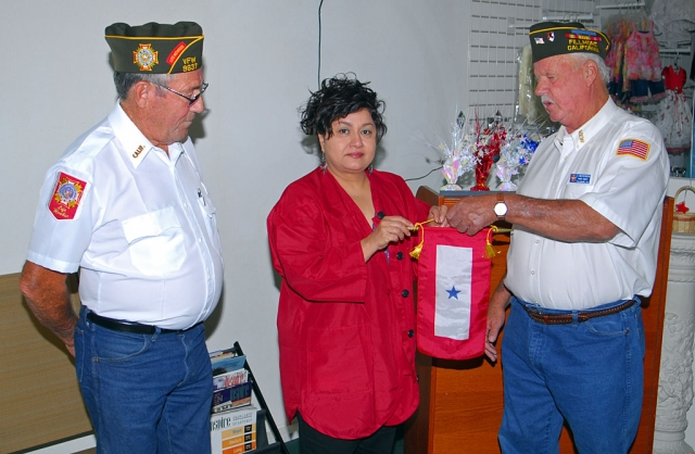 "Commander Jim Rogers and Jr. Vice Commander Vic Westerberg, VFW Post 9637 Fillmore, CA, present a Blue Star Banner to Esperanza Hurtado, mother of Staff Sgt. Alfredo Hurtado Jr. ""I would like to present you with this Blue Star Banner in honor of your son Staff Sgt. Alfredo Hurtado Jr. We would like to thank you and your family for all your sacrifices."" Note: Staff Sgt. Hurtado Jr. served in the United States Army in Mosul, Iraq in 2005 and received a Purple Heart& Bronze Star. He is now serving as a recruiter at Fort Guachuca, Arizona."