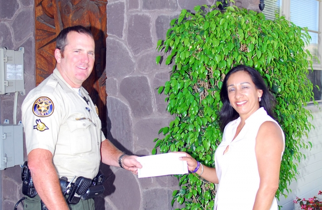Annette Fox accepts a check in the amount of $200 from Deputy Biter who represented the Sheriffs Association.