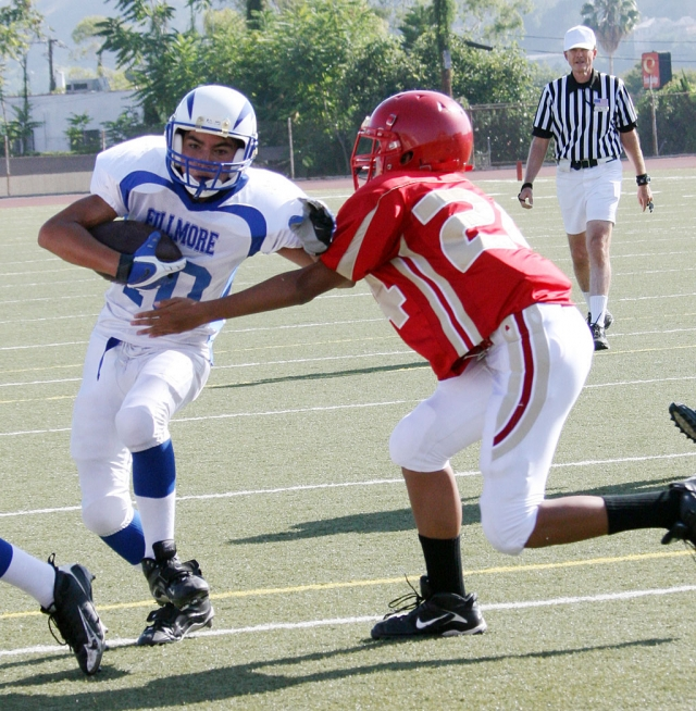 Mario Hernandez #10 (JV) puts his arm out to avoid the tackle. Hernandez also scored 1 touchdown.