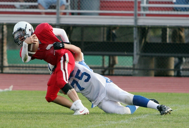 J.D. Smallwood #75 wraps up the J.V. Warrior player last Friday afternoon.