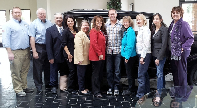 "The board of directors and officers in front of an ""antique"" automobile in the William L. Morris showroom. The participants are (l-r) Rick Neal, Ron Lewis, Jim Mendrala, Rosa Martel, Maria Christopher, Cindy Jackson, Kevin Keehl, Kathleen McCreary, Donna Stewart, Talia Wunder, Kathy Long."