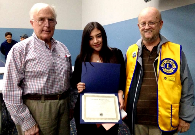 Pictured are Lions Club members Bill Dewey (left) and Brian Wilson with last year's Lions Club Student Speaker Contest winner Alina Herrera.