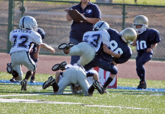 Fernando Gonzalez makes a punishing hit on a Oxnard ball carrier.