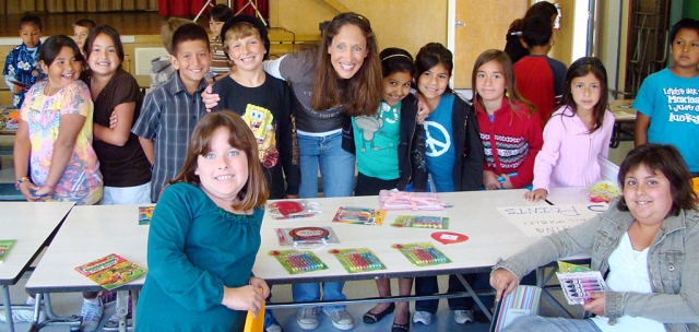 "Paula Phillips from the Dream Fund Outreach Foundation is shown with some San Cayetano students in a ""Rewards Store"" she set up in the school cafeteria. Students who have been recognized during the year as a Character Counts or Peacebuilder receives an invitation to ""Shop"" in the store. The school also celebrates with a pizza lunch for all students as San Cayetano is a school of service and each class has given back to our local community."