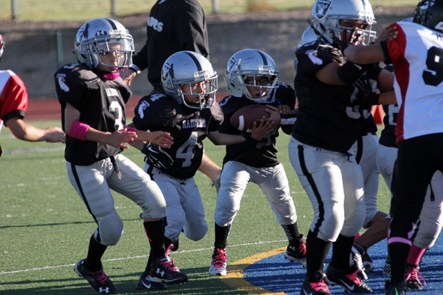 Raiders mighty mite's #3 and #4 make a path for #13 to make positive yardage