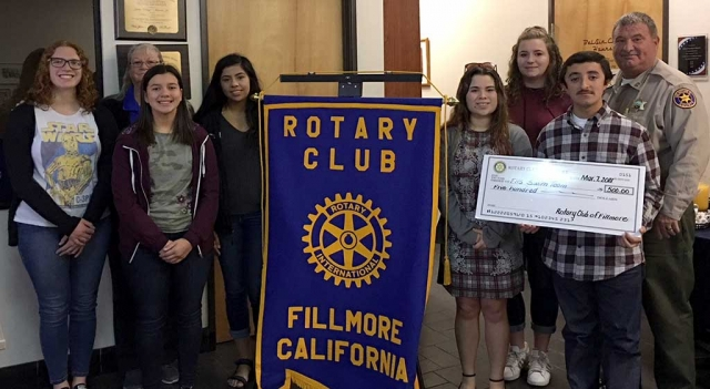 Fillmore Rotary Club donated $500 to the Fillmore High School Swim Team. Pictured are six team members along with their coach Cindy Blatt, accepting the donation from Rotary President Dave Wareham. Photo courtesy Martha Richardson.