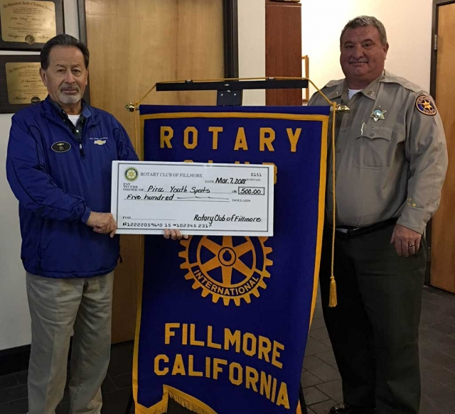 Pictured left is Gilbert Escoto who has been instrumental in establishing Piru Youth Sports, accepting a $500 check for the program from Fillmore Rotary Club president Dave Wareham. Photo Courtesy Martha Richardson.