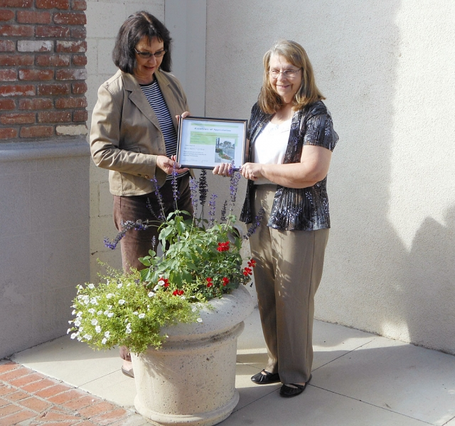 Sandi Ward (right) of Sandi Ward's Train Stop receiving her certificate of appreciation from Civic Pride Committee member, Linda Nunes.