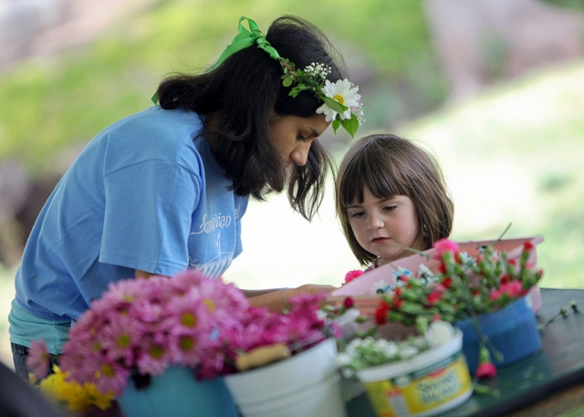A volunteer helps a child make a flower head wreath at the Scandinavian Festival at California Lutheran University. Photo by Erik Hagen/California Lutheran University.
