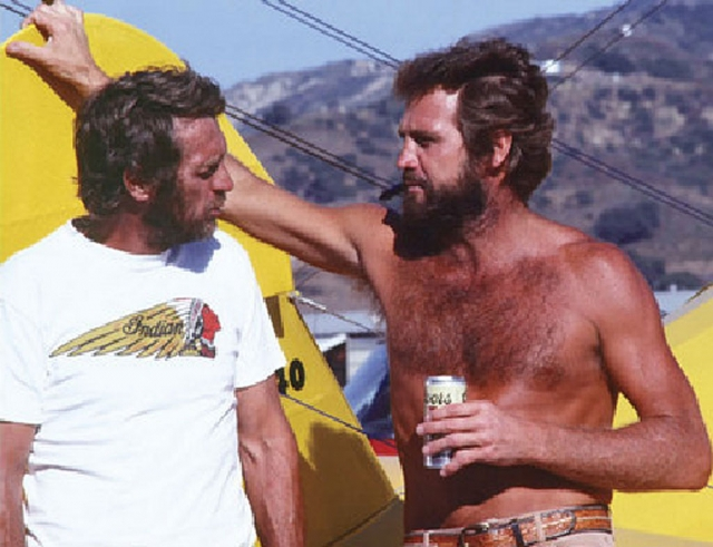 Steve McQueen and actor Lee Majors share a beer at the Santa Paula Airport, May 1979.