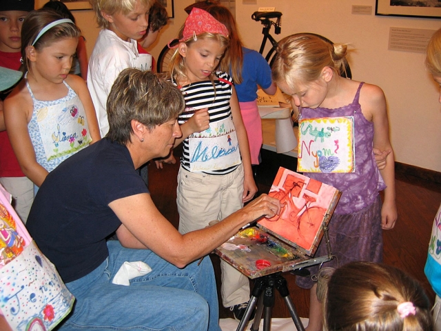 Artist Gail Pidduck demonstrates painting techniques to children at the Museum's Art Start program.