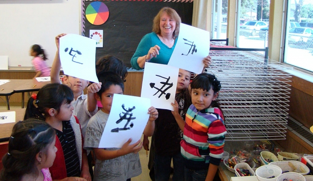 Art teacher and acclaimed local artist Virginia Neuman share some laughs with Mrs. Chambers first grade students in art class at San Cayetano.