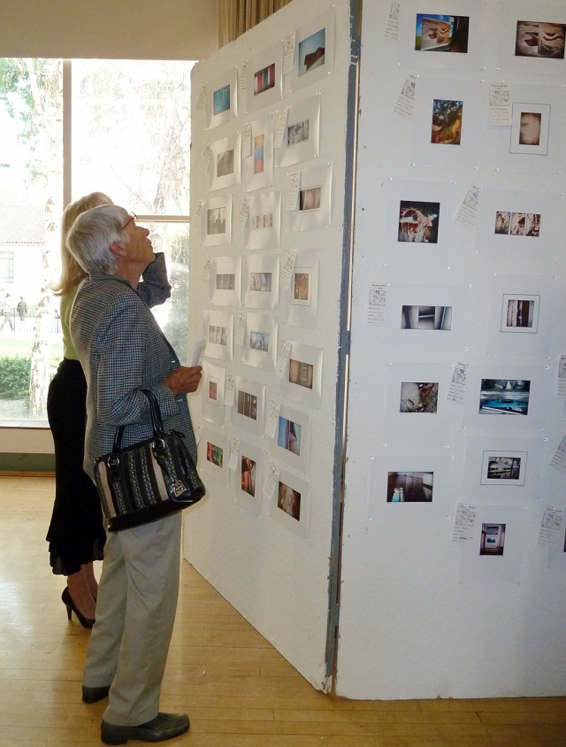 Sara Hansen and Jane David take a moment to view the pictures on display from photo class.