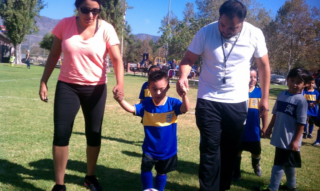 Escorted by his coaches, Emiliano Martinez scores a goal during his AYSO game.