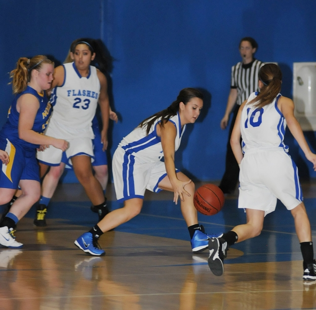 Kayla Grove #4 dribbles down court . Also pictured Mary Ortiz #23 and Ana Morino #10.