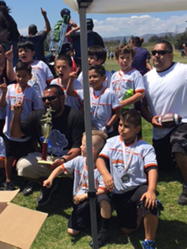 The Fillmore Broncos Flag Football team with their coach and trophy after winning division championship against Ventura last Sunday.