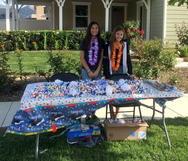 Aerin and Ashlee (l-r) are shown helping raise money for their sisters' Flashes Cheer, by selling 2019 graduation leis at the corner of River and Mountain View. Photo courtesy Katrionna Furness.