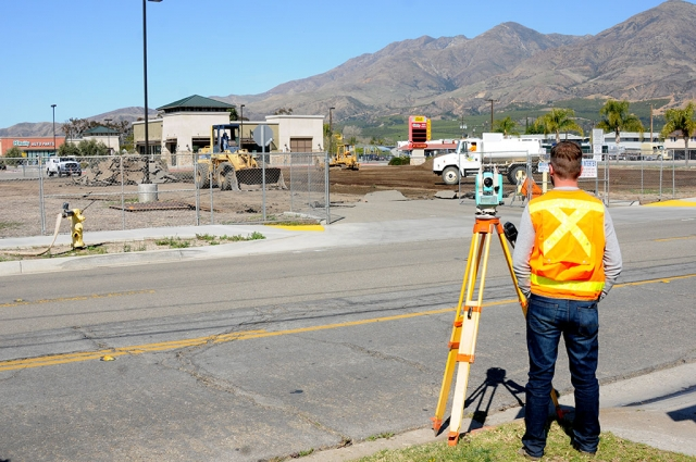 The empty lot located at the southwest corner of Highway 126 and C Street has been fenced in, preparing for new construction. Pictured is a surveyor watching the work being done.