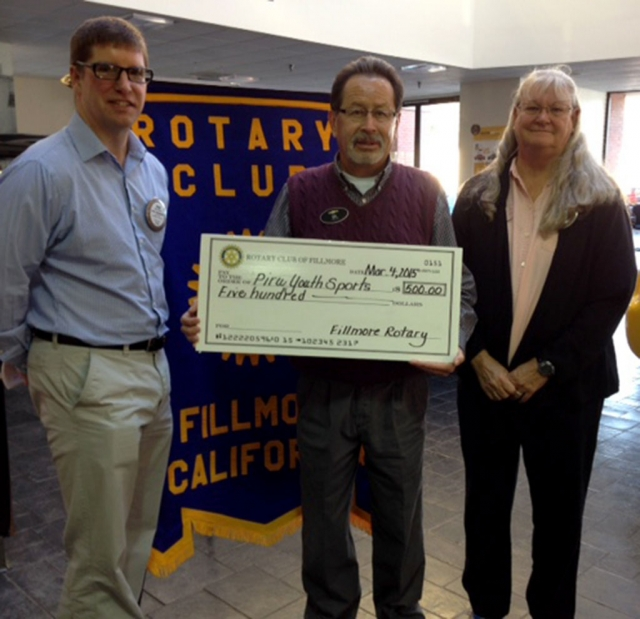 Gilbert Escoto accepted a check for Piru Youth Sports from Fillmore Rotary Club's Sean Morris and Cindy Blatt.
