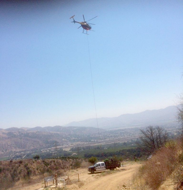 A helicopter loading some of the seized contraband onto a Sheriff 's vehicle.
