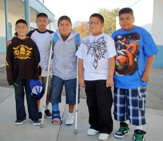 Fifth grade students back to school at San Cayetano surround fellow 5th grader, Fernando, who injured his foot playing football.