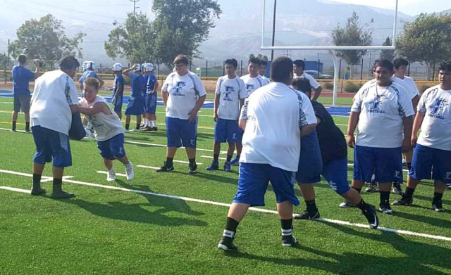 Fillmore High School JV and Varsity Football teams preparing for the upcoming season. They were seen going through wide base, head up, and short choppy steps drills together.