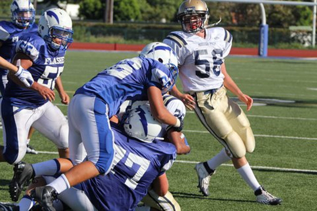 Fillmore Flashes JV players David Cadena #26 and Chad Petuoglu #77 tackle Mission Prep's runner.