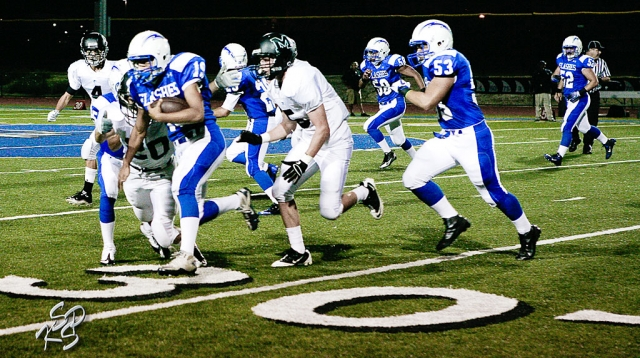 "Daniel Cruz (#19) trys to stay away from Malibu's defense with the help of Brandon Pina (#63). Pina attributed 9 tackles to the game. Also, Sammy Orozco had 7 tackles and Joseph De La Mora had 12 tackles. According to Coach Dollar, ""We had too many penalties. For many of the players it was their first Varsity start. We still have many things that we need to improve on."""