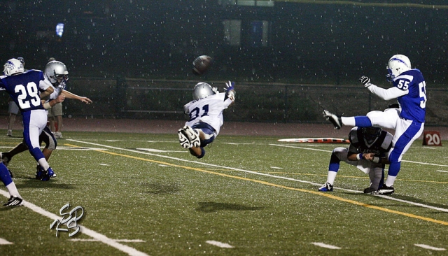 Frazier Mountain's player dives in the rain to block the punt kicked by Lalo Gomez. Robert Bonilla had two interceptions, one for a touchdown. Joseph De La Mora had 12 tackles and an interception.