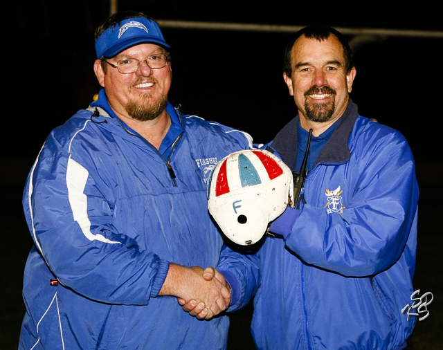 Coach Matt Dollar and Principal John WilbEr hold the leather helmet for the camera. Fillmore defeated Santa Paula last Friday night. It has been 2 years since we have had the helmet in Flashes territory. Photo by Carmelita Miranda, KSSP Photographic Studios, Fillmore.