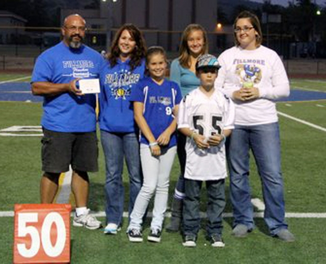 Max Pina Jr. presents a thank you plaque to the family of Walker Kozar at the beginning of Friday night's varsity football game. The plaque will be hung in the BBQ area by the stadium snackbar, honoring Kozar's years of barbecuing for the games.