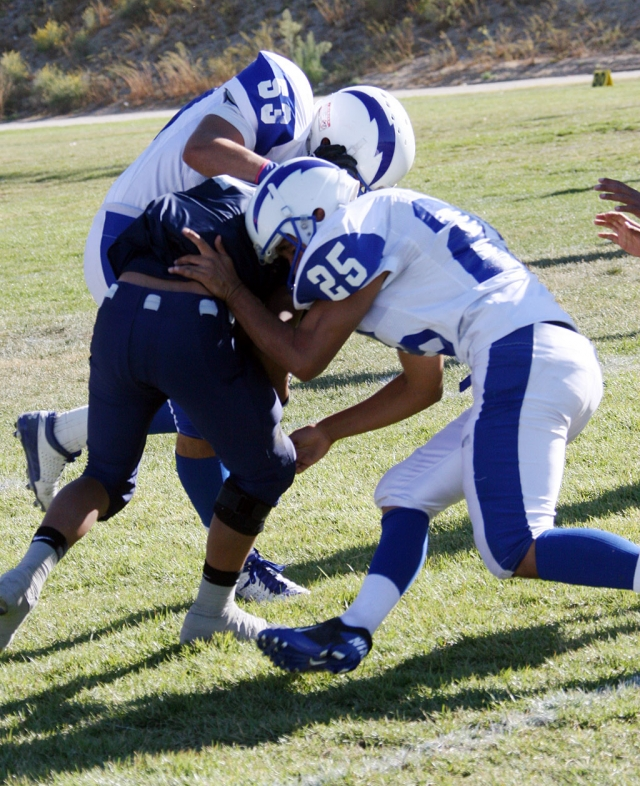 George Orozco #53 and Alex Banales #25 make a great tackle to bring down Frazier Park's runningback.