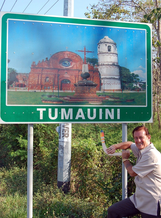 Photo of John next to the Tumauini road sign.