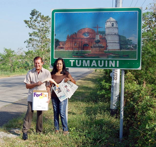 Another photo of John next to the Tumauini road sign with Ester.