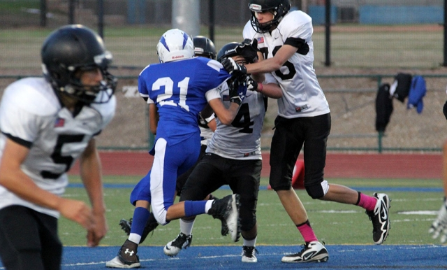 #21 Dylan Satterfield wards off two defenders to make the tackle