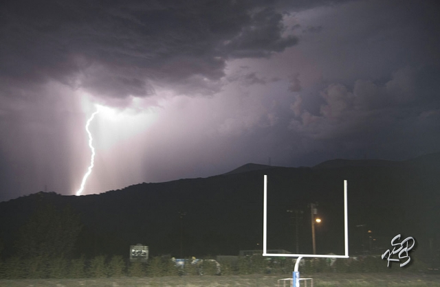 A bolt of lightning struck the Sespe Mountains this past Friday evening, delaying the football game by 30 minutes. [Photo by KSSP Photographic Studio]