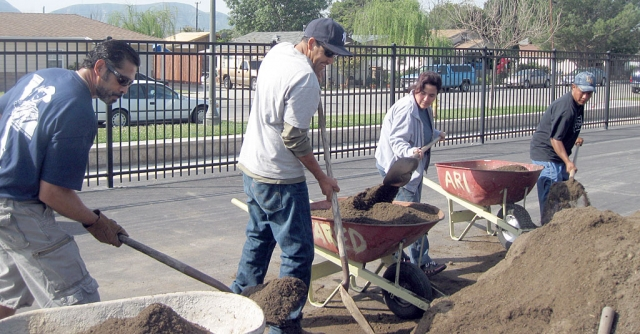 Mountain Vista parent volunteers, Mr. Castro, Mr. Vargas, Mrs. Aparicio, and Mr. Magana shoveling 19 cubic yards of soil to fill the planter boxes. Classrooms will have the opportunity to plant vegetables and help maintain the garden.