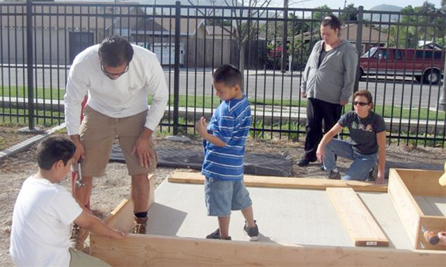 Getting Ready for Spring, Mountain Vista Elementary School planned a garden workday. Staff and Parents volunteered their time on two Saturdays to assemble planter boxes and fill them with soil.  getting them ready for classrooms to begin planting. Pictured are Darren and Joey Zepeda helping Mr. Castro level a planter box as Mrs. Castro and Marie  Molina look on.