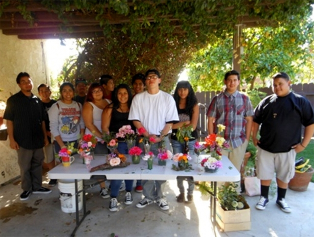 One Step A La Vez teens display their creations at a workshop led by Civic Pride committee members to engage Fillmore's youth to enter the flower show and practice making an arrangement.