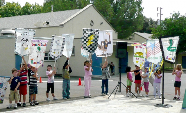 "(Above) Opening Ceremony with class banners of the Piru Elementary Olympics. ""Citius, Altius, Fortius,"" last week the Olympic Motto came to life for students at Piru Elementary as they reached for ""swifter, higher, and stronger"" achievements in their school Olympics. After practicing at lunch recess for weeks at their Olympic Training Center the student athletes were ready to meet the competition. The Games began with a grand procession of classes around the athletic field to the Opening Ceremonies. While their class banners proclaimed their class' presence students were welcomed to the competition in the spirit of the Olympics. Following the lighting of the Olympic flame the opening day competition began.  To classmate cheers athletes pulled with all their strength in the tug-of-war competition and later ran swiftly in a shortened marathon. Winners were awarded ""Olympic"" medals for their success. Throughout the week at lunch recess the competition continued when grade levels vied for soccer medals.  Piru's Olympic Games culminated Friday afternoon as individual students and teams gave their best as they struggled for success in long jump, shot put, jump rope, hula hoop, Frisbee throw, and running relay. As the games drew to a close every student had an opportunity to compete to the encouragement of his or her classmates. And, Piru Elementary School echoed with the pleasure of its students."